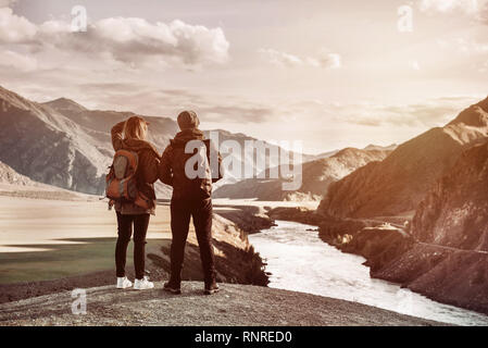 Couple of travelers stands on viewpoint and looks at mountains and river from viewpoint. Travel concept with space for text - Stock Image