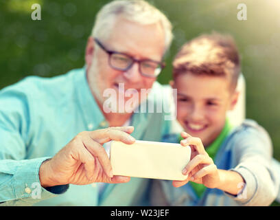 old man and boy taking selfie by smartphone - Stock Image
