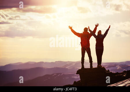Happy couple sunset winners mountain top - Stock Image