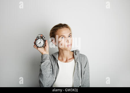 Portrait Handsome Young Woman Posing Blank White Background.Pretty Girl Smiling Holding Vintage Alarm Clock Hand - Stock Image