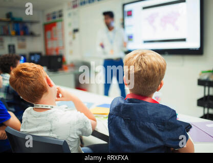 Junior high school boys watching teacher during lesson in classroom - Stock Image