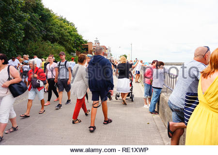 Kolobrzeg, Poland - August 10, 2018: Many people standing and walking on a promenade along the beach on a cloudy day. During high season this location - Stock Image