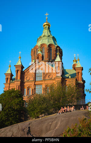 Uspenski Cathedral Helsinki, view of the Russian Orthodox Uspenskin Katedraali in Helsinki with young people watching a summer city sunset, Finland. - Stock Image