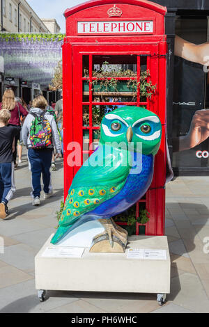 PeafOWL, one of Minervas Owls of Bath in front of a red telephone box used as a planter/greehouse in Southgate shopping area Bath - Stock Image