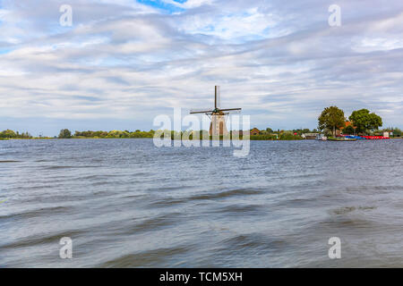 Landscape with clouded sky and a old Dutch traditional windmill located at Rottemeren lake near Rotterdam. - Stock Image