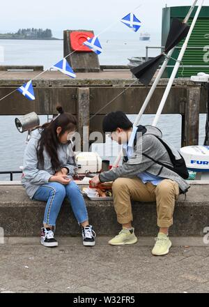 Asian tourists sharing a seafood platter on the harbour wall in Oban, Scotland, UK, Europe - Stock Image