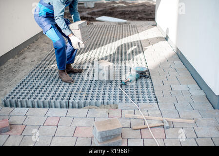 Builder carrying paving tiles on the construction site, cropped image with no face - Stock Image