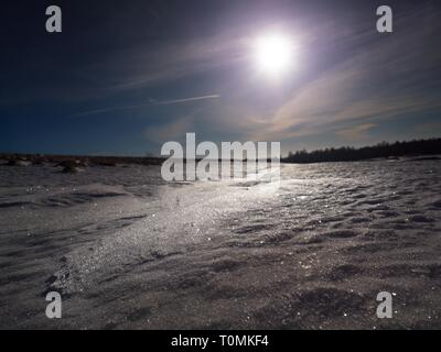 Snow with light reflections from cold winter sun. Snowflakes and shadows detail - Stock Image