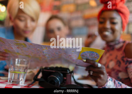 Young women friends looking at map on vacation in restaurant - Stock Image