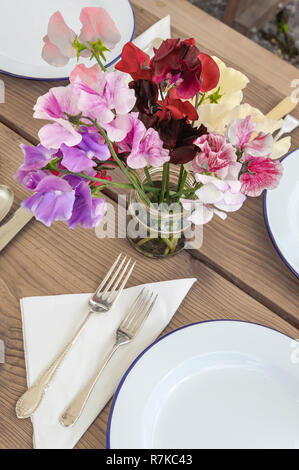 UK. A jam jar filled with freshly picked sweet peas decorates a garden table laid for a simple outdoor meal in summertime - Stock Image