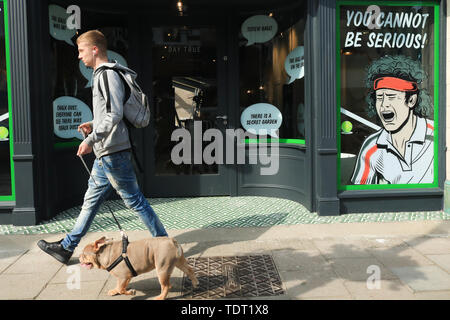 Wimbledon London, UK. 18th June, 2019. Pedestrians walk past a shop in Wimbledon High Street decorated with a caricature of John McEnroe shouting his famous expletive ' You cannot be serious' as Wimbledon prepares to host  2019  Tennis championships on 1st July Credit: amer ghazzal/Alamy Live News - Stock Image
