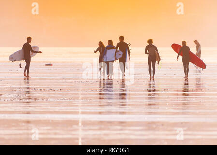 A group of surfers carrying their surfboards and walking across Fistral Beach in late evening sunshine. - Stock Image