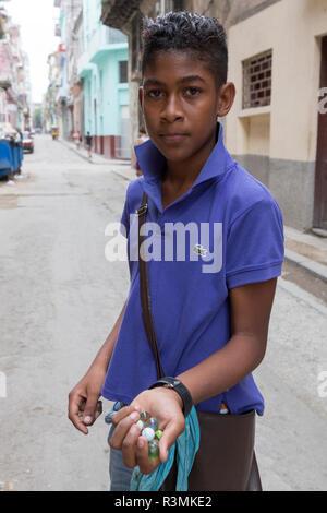 Cuba, Havana, Old Havana. Boy holding glass marbles. Credit as: Wendy Kaveney / Jaynes Gallery / DanitaDelimont.com - Stock Image