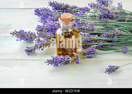 Lavender essential oil with a bouquet of lavender flowers on a rustic wooden background with a place for text - Stock Image