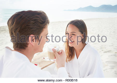 Young couple drinking coffee on beach - Stock Image
