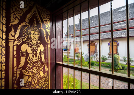 Gold-painted Buddha image on a wooden shutter inside the main Wiharn of Wat Chiang Man, Chiang Mai, Thailand - Stock Image