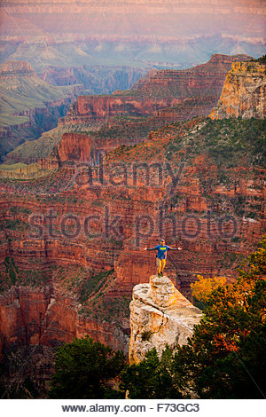 Man Standing on the Edge of the North Rim of the Grand Canyon with arms spread expressing the immensity of nature - Stock Image