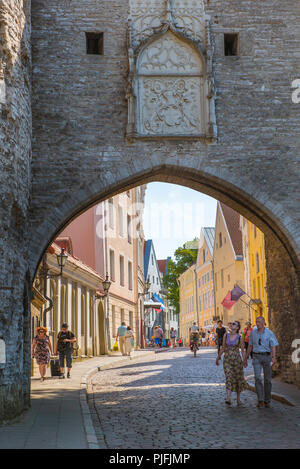 View of people walking under the arch of the Great Coast Gate on Pikk street at the north side of the medieval Old Town quarter in Tallinn, Estonia. - Stock Image