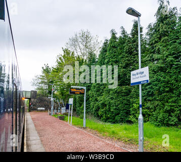 Roy Bridge rural train station platform and name sign with ScotRail train on West Highland railway line, Scottish Highlands, Scotland, UK - Stock Image