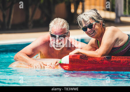 Happy joy cheerful people adult senior couple have fun in the swimming pool with trendy coloured lilos mattress on a blue water in hotel resort for su - Stock Image