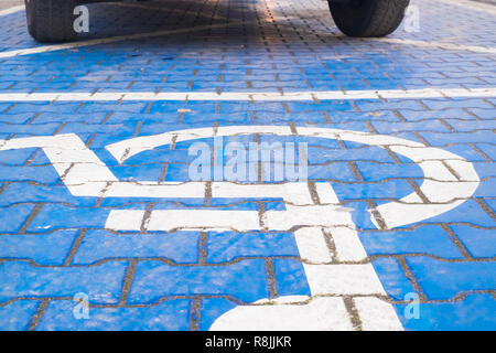 two wheels on the disabled dedicated parking place marked with blue wheel chair symbol - Stock Image