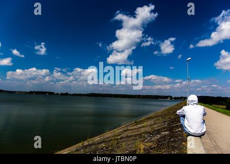Man with a white hoodie sitting on the wall near Goczałkowice Lake, Poland. - Stock Image