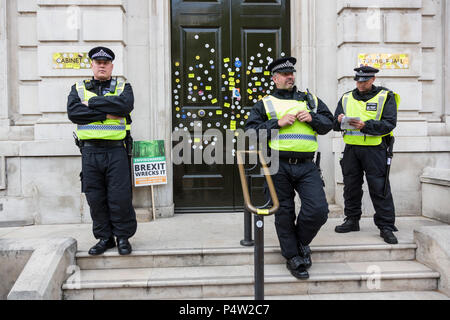 London, UK. 23 June 2018.Anti-Brexit march and rally for a People's Vote in Central London. Policemen guard the front door of the Cabinet Office after it had been defaced with stickers by protesters. - Stock Image