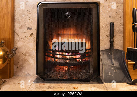 A typical modern fireplace with wood burning and a metal mesh guard, UK - Stock Image