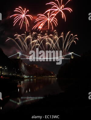 Bristol, UK. 07th Dec, 2014. Red and gold fireworks being fired from Bristol`s famous Clifton suspension bridge - Stock Image