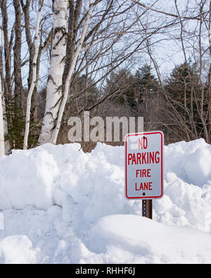 'No Parking Fire Lane' sign on snow bank near the Sacandaga River in Speculator, NY keeping the area open for fire trucks to draw water from the river - Stock Image