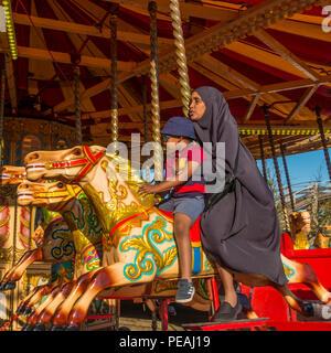 Muslim woman,Adult,Child,Riding,Carousel,Dreamland,Margate.Kent,England,UK - Stock Image