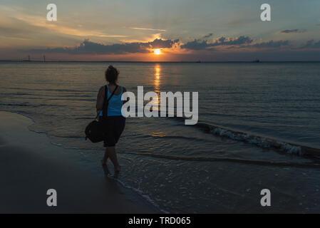 Woman walking on Jekyll Island, Brunswick Georgia at Sunset - Stock Image