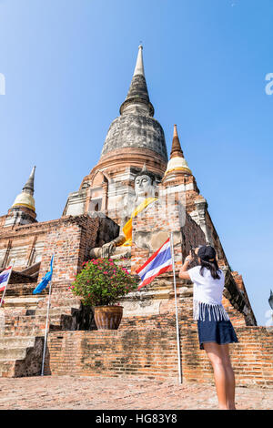 Tourist teenage girl standing take a photo of buddha statue and ancient pagoda on blue sky background at Wat Yai - Stock Image