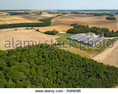 Aerial landscape of farm buildings harvested summer wheat and barley fields and forest trees - Stock Image