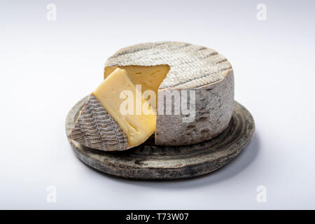 Round mature French Tomme cheese with one cutted piece on grey stone plate isolated close up - Stock Image
