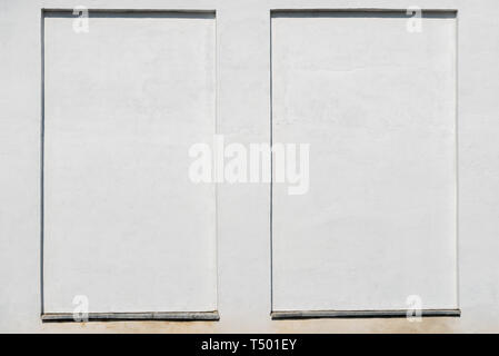 weathered white stucco wall with a stucco frame. - Stock Image