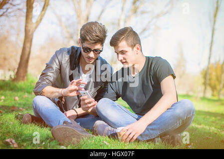 Friends in the park laughing and looking at cell phone - Stock Image