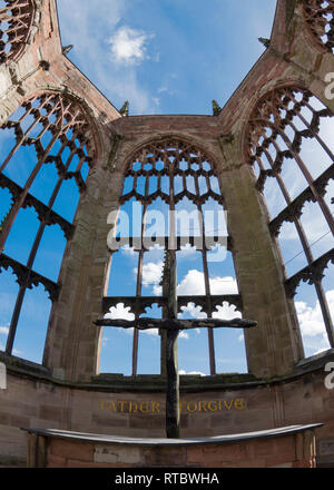 Dramatic view of the ruins of the old gothic Coventry Cathedral framed against the sky with the Cross of Nails. - Stock Image
