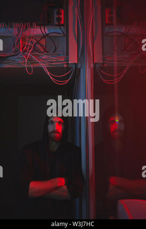 Portrait of serious confident young bearded hacker in hoodie leaning on wall in server room with Ethernet hub - Stock Image