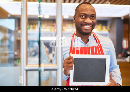 African waiter with empty blackboard in his hands in the restaurant - Stock Image