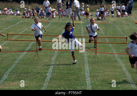 primary school sports day, children jumping hurdles - Stock Image