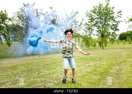 Young boy trailing a blue smoke flare in a park running across the lawn with a beaming smile of pleasure and enjoyment - Stock Image