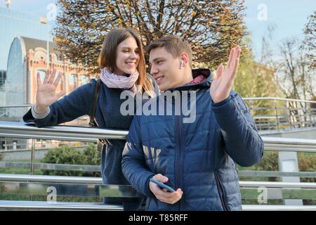 Happy young couple of students gives high five, spring city background. - Stock Image