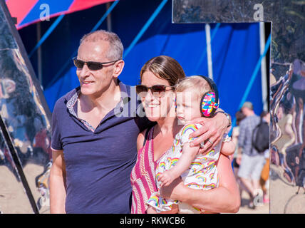 A smiling couple with a pensive baby pose for the camera in front of a huge reflective latitude sign at the Latitude Festival 2018. - Stock Image