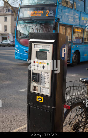 A parking meter in St. Giles. Oxford with a double decker Oxford City bus passing by - Stock Image