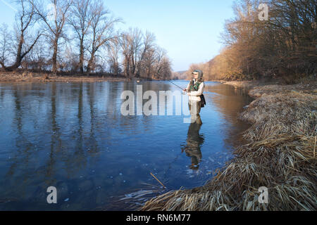 A young attractive woman is fishing with a spinning standing in a river on a clear spring sunny day. - Stock Image