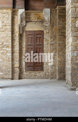 Facade of old abandoned stone bricks wall with grunge weathered wooden door, Old Cairo, Egypt - Stock Image