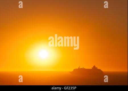A cruise ship leaves Cádiz bay at sunset. - Stock Image