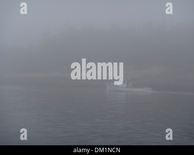 A lone lobster boat heads home in the heavy fog in downeast Maine. - Stock Image