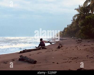 One woman sitting on a log on an empty deserted beach - Stock Image